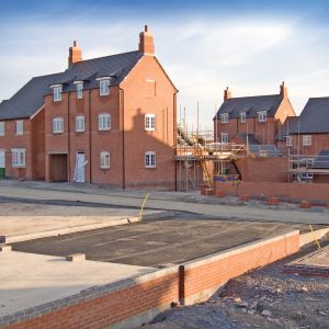 New homes in the process of being built with foundations in the foreground set against a blue sky