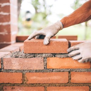 professional construction worker laying bricks and building barbecue in industrial site. Detail of hand adjusting bricks